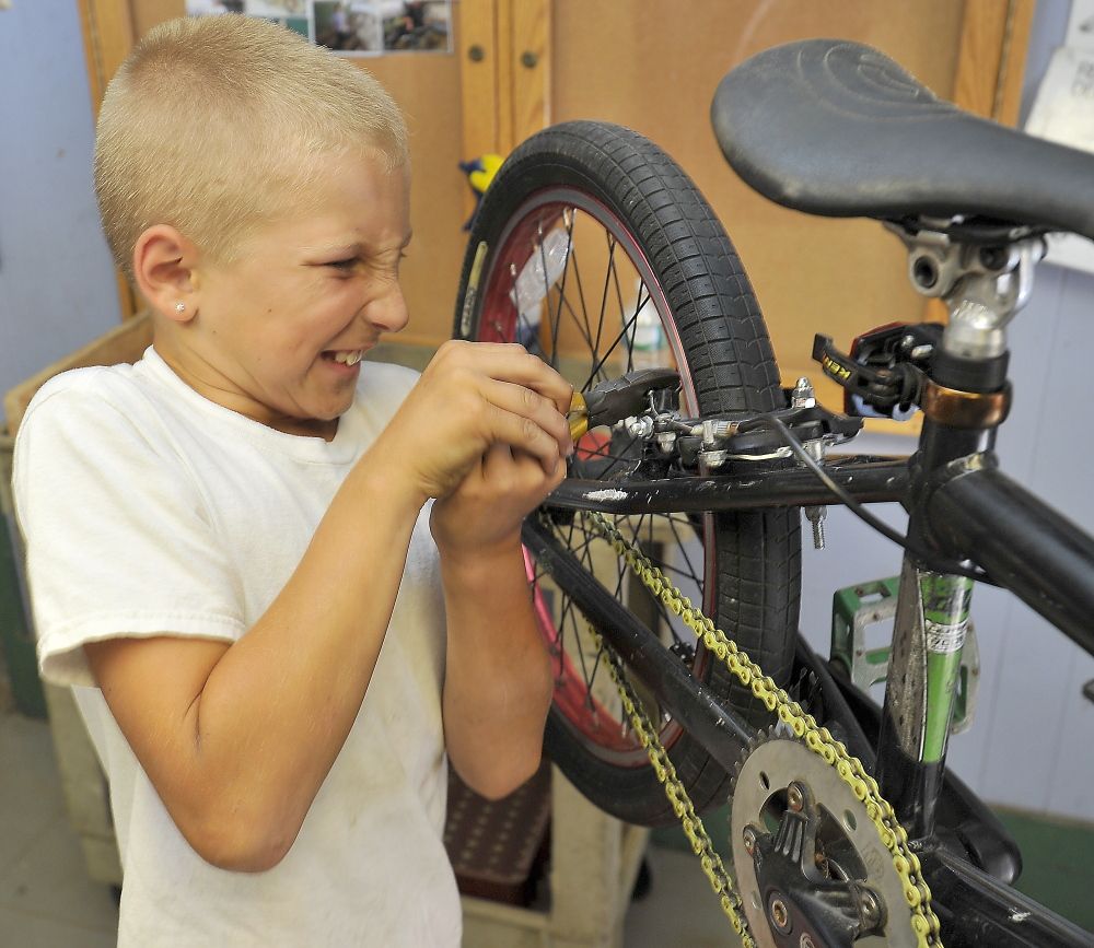 Ten-year-old Austin Cantara pulls hard on the wrench as he tightens a nut on the brake pad that he just replaced on his bike in the Community Bicycle Center, a non-profit agency in Biddeford. The agency prepares to leave its old site on Hill Street and move to a larger building a few blocks away.
