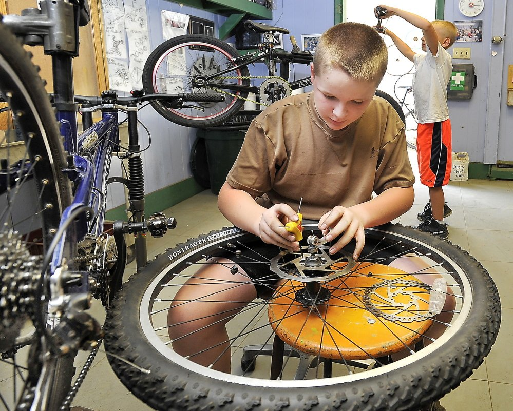 Cameron Roy, 13, works on a rear wheel at the Community Bicycle Center, a non-profit agency in Biddeford, that is preparing to leave its old site on Hill Street and move to a larger building several blocks away.