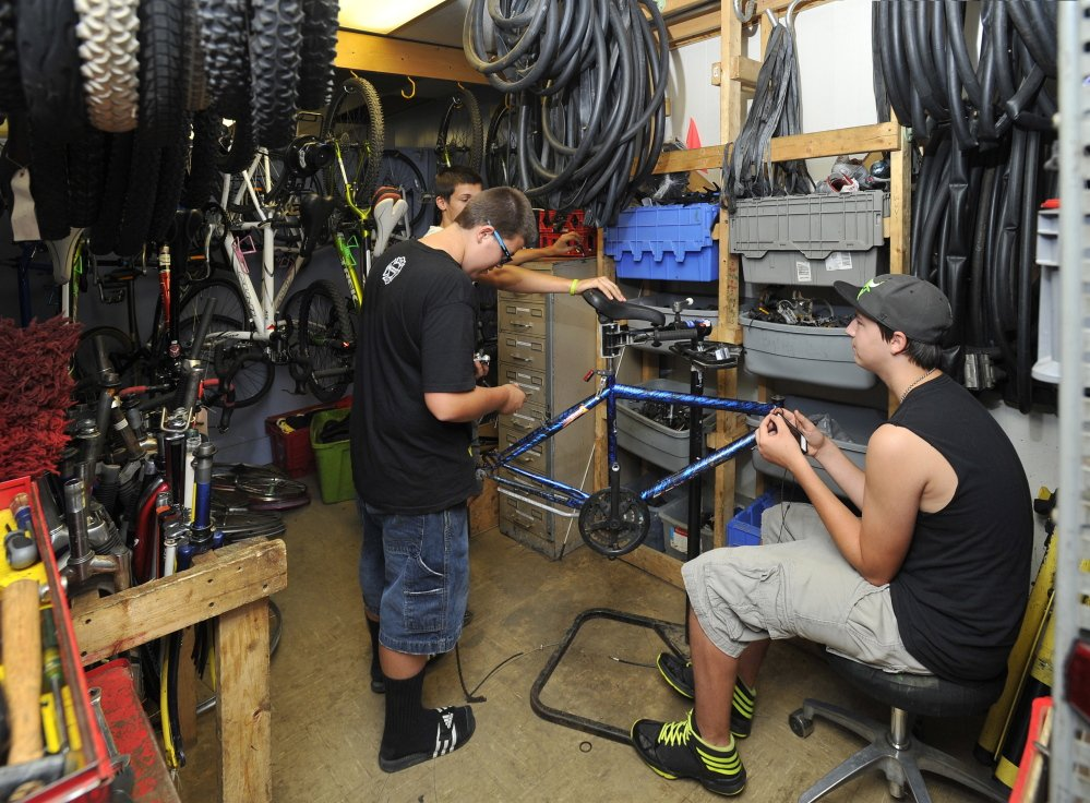 Three volunteers work in a cramped parts room refurbishing a bike at the Community Bicycle Center, a non-profit agency in Biddeford. The agency will leave its old site on Hill Street in September and move to a larger building several blocks away.