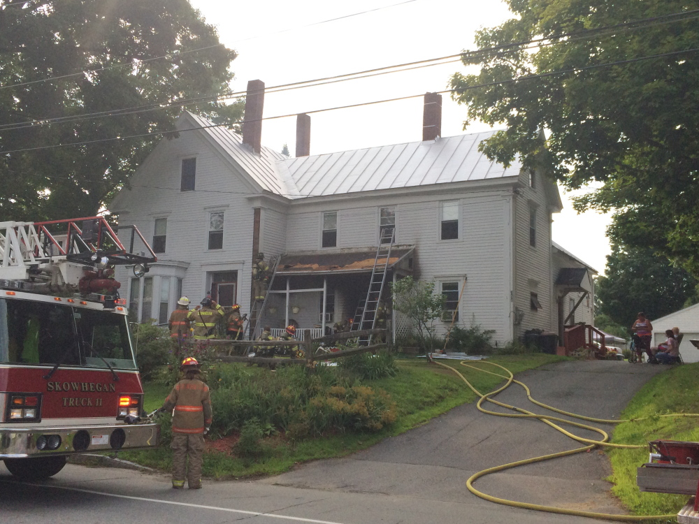 Evelyn McElrath, 89, who uses an oxygen tank, was led from her home on Water Street in Skowhegan by her niece, Sonya Fox, when an improperly disposed cigarette caused a porch fire that damaged the exterior of the house on Monday in Skowhegan.