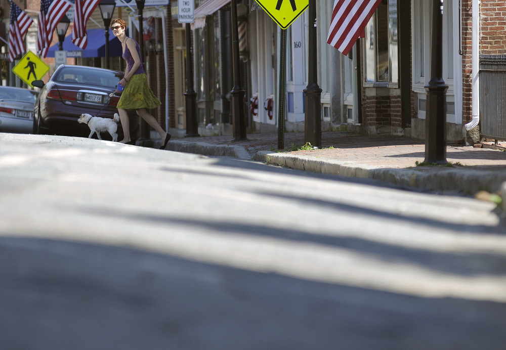A woman walks her dog on June 9, 2014, across Water Street in Hallowell. Downtown business owners are concerned that a months-long project to rebuild the steeply crowned road will mean a significant loss of business, but city and state transportation officials say the work to level the road is long past due.