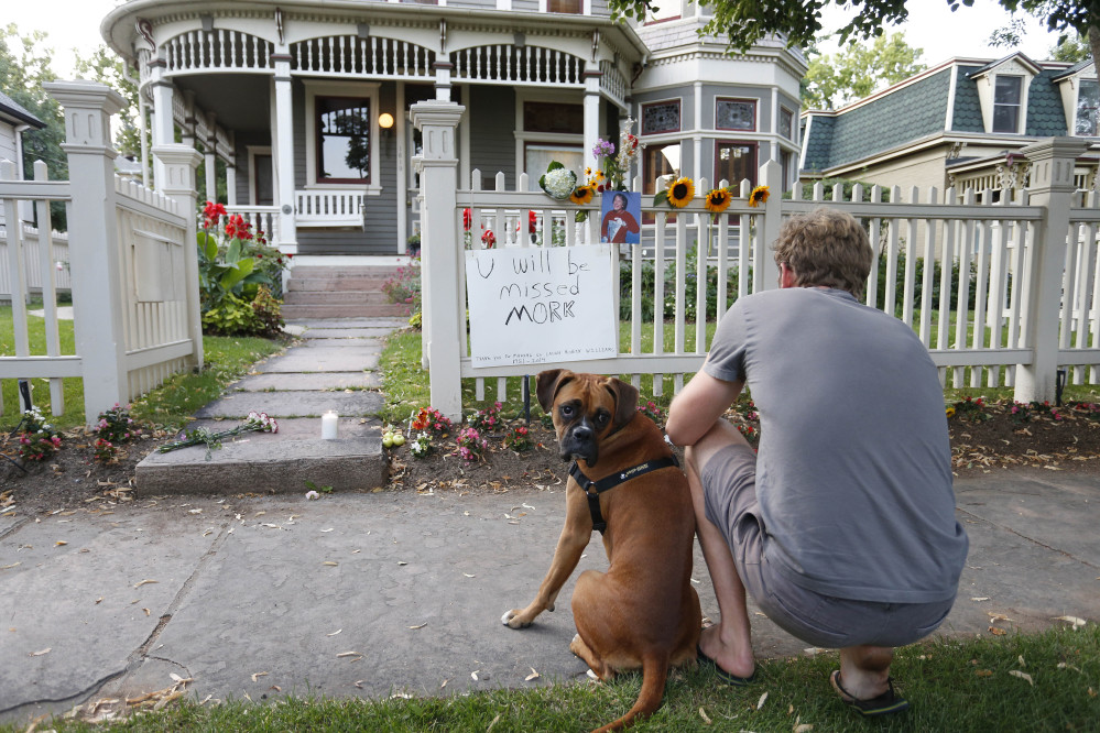 Caine Delacey, of Australia, with his dog Dia, takes a picture at the home where the 80s TV series Mork & Mindy, starring the late Robin Williams, was set, in Boulder, Colo., Monday.