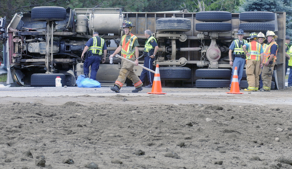 Police and firefighters converge Tuesday on an overturned dump truck on U.S. Route 202 in Winthrop.  The operator pulled over, according to police, to yield to an ambulance when he lost control.  The driver suffered bumps and bruises, state police said, but did not wish to be transported to a hospital. Traffic was reduced to one lane on the road as crews prepared to right the truck.