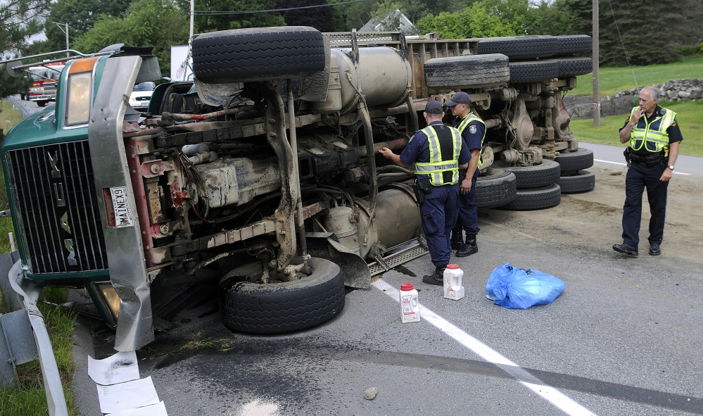 Police inspect an overturned dump truck Tuesday on U.S. Route 202 in Winthrop.  The operator pulled over, according to police, to yield to an ambulance when he lost control.  The driver suffered bumps and bruises, police said, but did not wish to be transported to a hospital. Traffic was reduced to one lane on the road as crews prepared to right the truck.