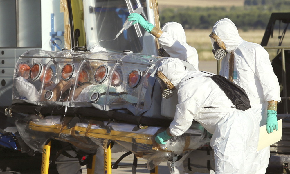 In this Aug. 7, 2014 file photo provided by the Spanish Defense Ministry, aid workers and doctors transfer Miguel Pajares, a Spanish priest who was infected with the Ebola virus while working in Liberia, from a plane to an ambulance as he leaves the Torrejon de Ardoz military airbase, near Madrid, Spain.