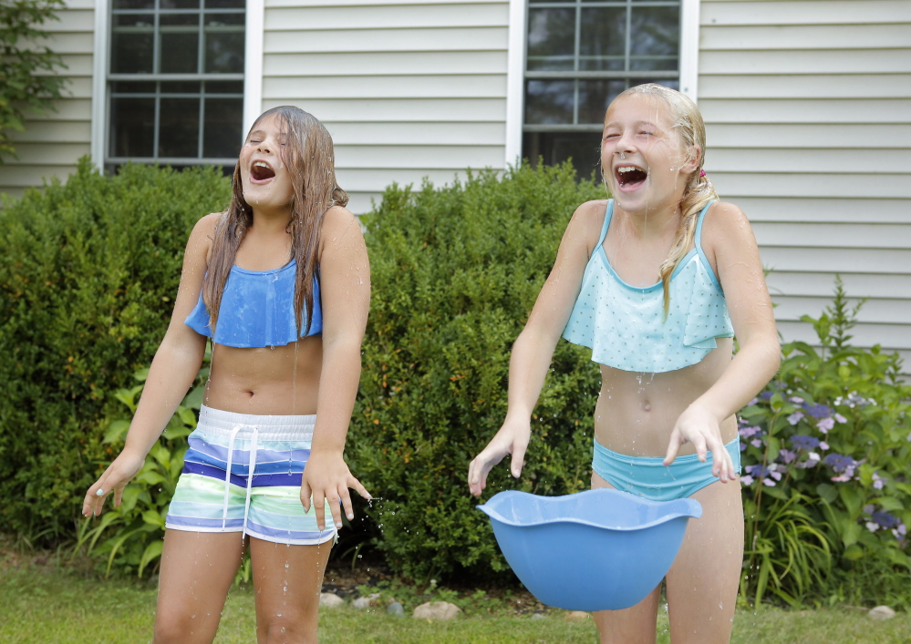 Matilda Bordas, left, and Rowan Pow, both 9, dump buckets of ice and water on their heads Tuesday in Kennebunk after being nominated by a friend in the ALS Ice Bucket Challenge, which aims to raise money to fight amyotrophic lateral sclerosis through social media.