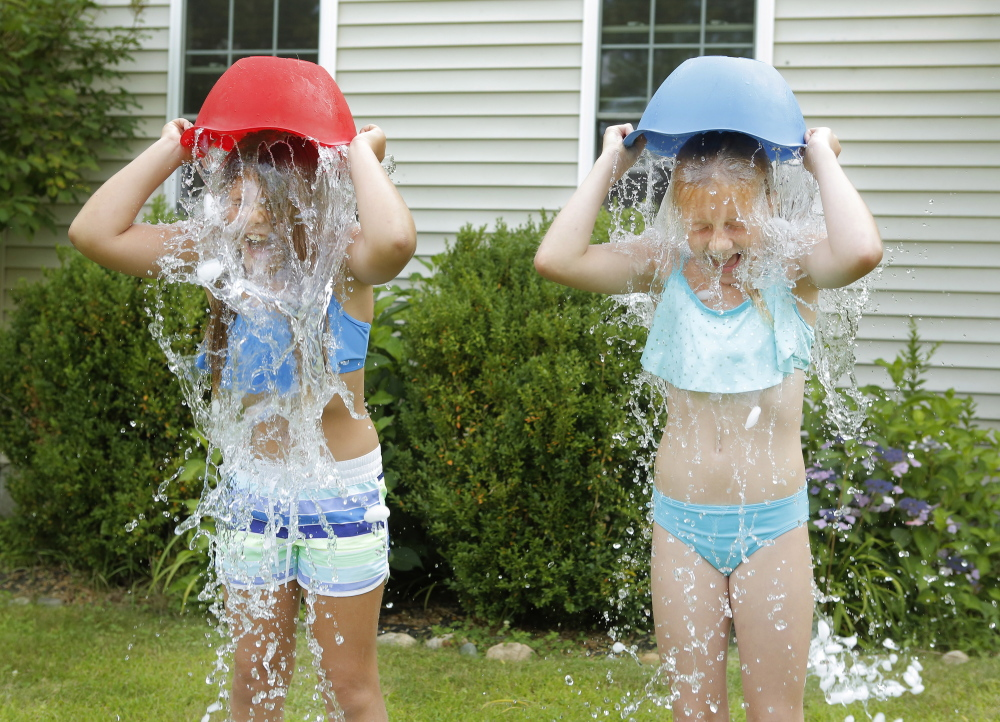Matilda Bordas, left, and Rowan Pow, both 9, dump buckets of ice and water on their heads Tuesday in Bordas's front yard in Kennebunk. The were nominated by a friend in the ALS Ice Bucket Challenge, which is using social media to raise money to fight amyotrophic lateral sclerosis, or Lou Gehrig's disease.