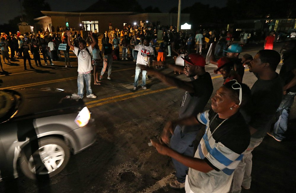 A group demonstrates along and in the middle of Chambers Rd. outside the Greater St. Mark Missionary Baptist Church after the conclusion of a gathering with Michael Brown's family and Rev.