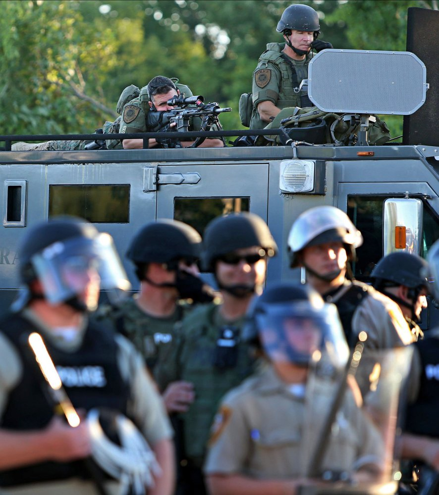 A police sharp shooter keeps an eye on protesters along W. Florissant Avenue on Tuesday, near the QuikTrip that was burned down a few days earlier in Ferguson.