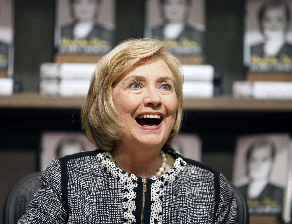 """The Associated Press This July 29, 2014, file photo shows former Secretary of State Hillary Rodham Clinton as she greets a customer during a book signing of her new book """"Hard Choices"""" at Northshire Bookstore in Saratoga Springs, N.Y."""