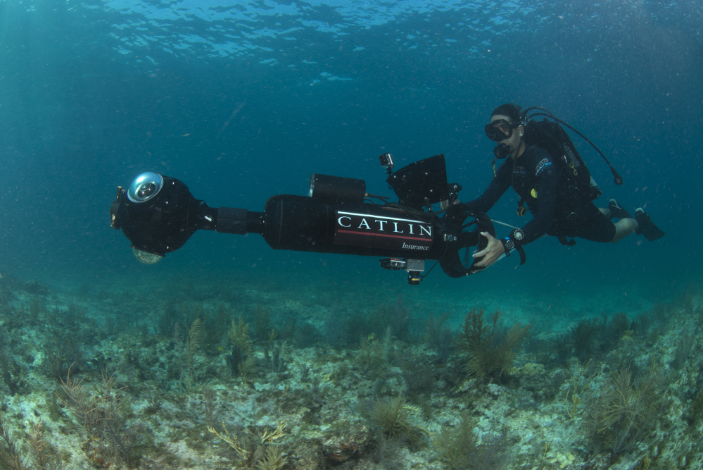 "In this Aug, 9, 2014 photo provided by Catlin Seaview Survey, Catlin's Manuel Gonzalez surveys an area underwater in Key Largo, Fla. U.S. government scientists hope people will soon be able to go online and get a 360-degree view of reefs and other underwater wonders, much like Google Map's ""street view"" lets people look at homes."