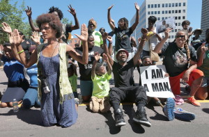Protesters drop to their knees and put their arms in the air during a rally for Michael Brown Jr., who was shot and killed by a Ferguson, Mo., police officer on Aug. 9.