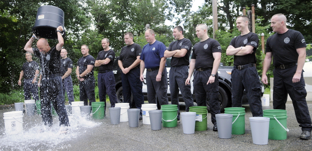 Augusta Police Sgt. Christian Behr pours a bucket of ice water over his head in the agency's parking lot as part of a challenge to raise money for ALS research. Several officers took the ice bucket challenge.