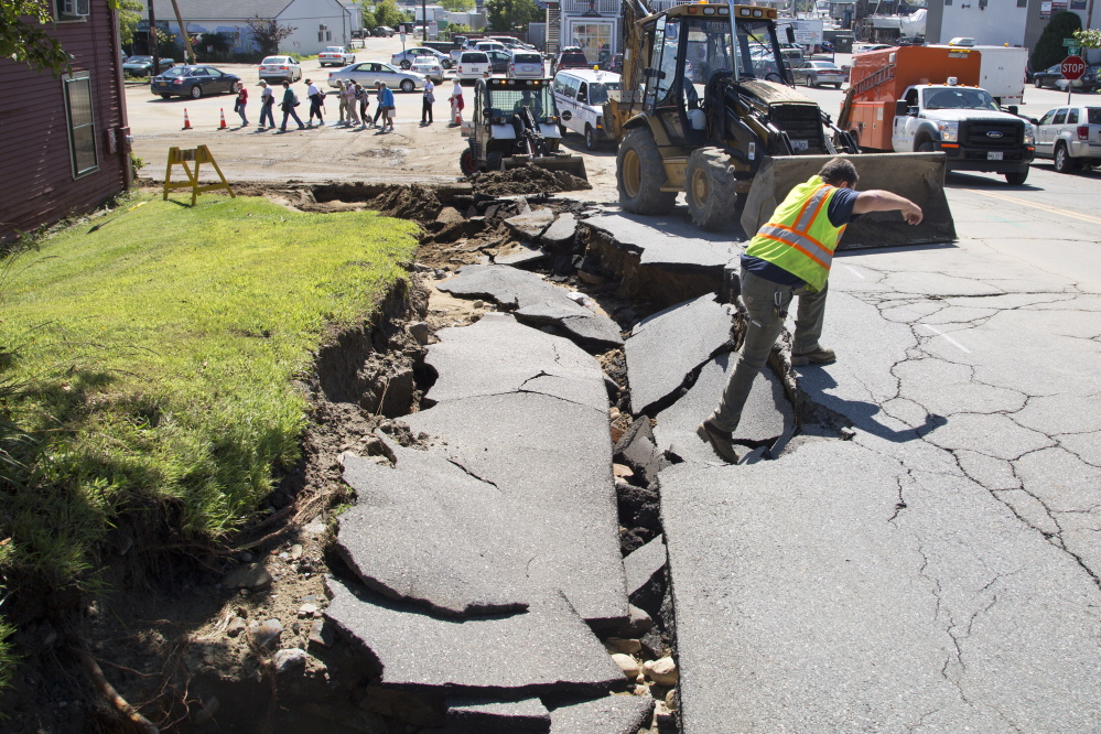 PORTLAND, ME - AUGUST 14: Utility workers surveyed and dug out a hole in front of Rufus Deering Lumber on Commercial St. the day after heavy rains and flash flooding on Thursday, August 14, 2014. (Photo by Yoon S. Byun/Staff Photographer)