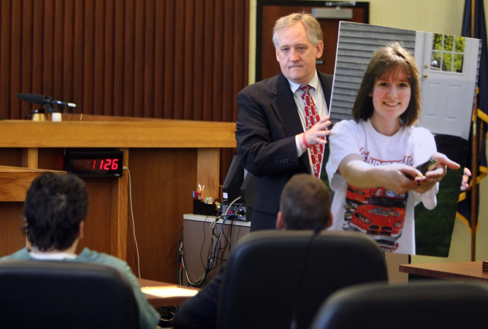 "Bob Marriott holds a large photo of his daughter Elizabeth ""Lizzy"" Marriott as he looks at Seth Mazzaglia, seated left, during a sentencing hearing in Strafford County Superior Court on Thursday in Dover, N.H."