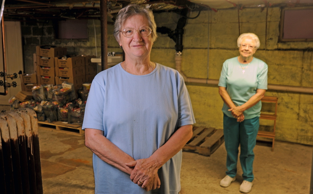 Louise Carl, foreground, food pantry coordinator at the Bingham Area Food Pantry, and long-time volunteer Rita Seguin, background, stand amid the dwindling supplies of food in the Bingham Area Food Pantry in the basement of the St. Peter Church rectory in Bingham on Thursday. The pantry is shutting down after 33 years because the building is being sold.