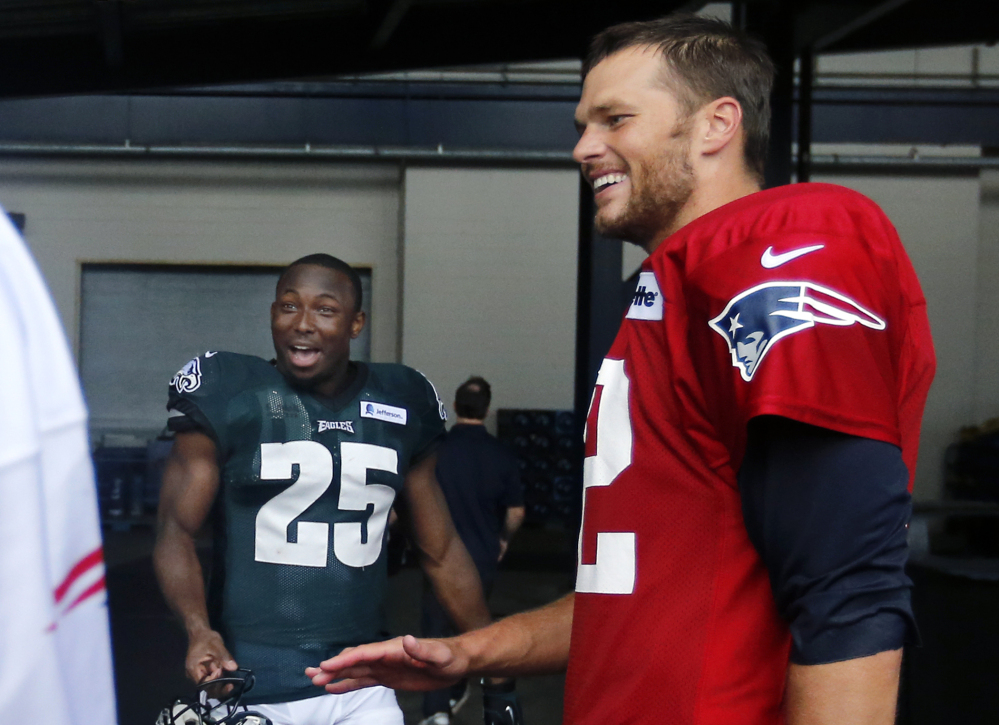 New England Patriots quarterback Tom Brady, right, and Philadelphia Eagles running back LeSean McCoy (25) chat after a joint NFL training camp practice Wednesday in Foxborough, Mass.