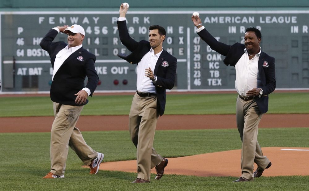 Boston Red Sox greats Roger Clemens, Nomar Garciaparra and Pedro Martinez, from left, throw out the ceremonial first pitch prior to Thursday's game at Fenway Park in Boston. Clemens, Garciaparra and Martinez were inducted into the Boston Red Sox Hall of Fame earlier in the day.