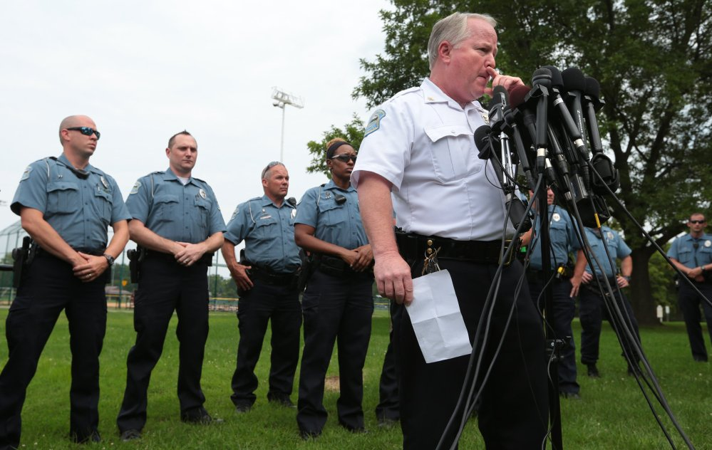 Ferguson Police Chief Tom Jackson is surrounded by his officers at a news conference Friday. Jackson took questions from the media after identifying Darren Wilson as the officer who shot Michael Brown.