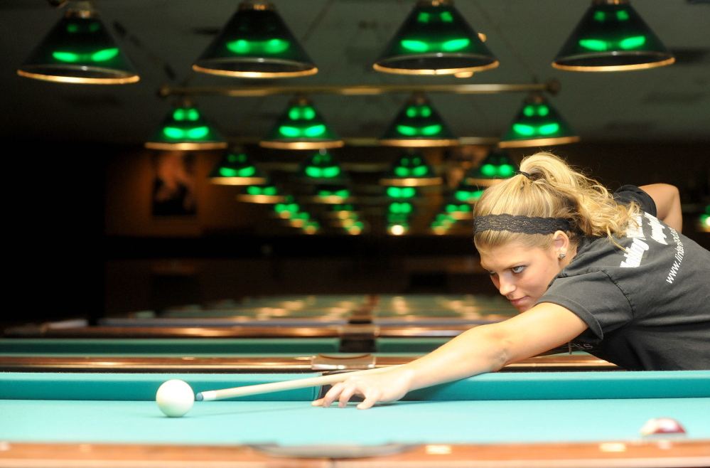 Photo by Michael G. Seamans/Staff Photographer Taylor Reynolds, a senior at Lawrence High School, lines up a shot during a game of billiards Friday at TJ's Billiards in Waterville. Reynolds is also taking aim at the junior world title November in Shanghai, China.