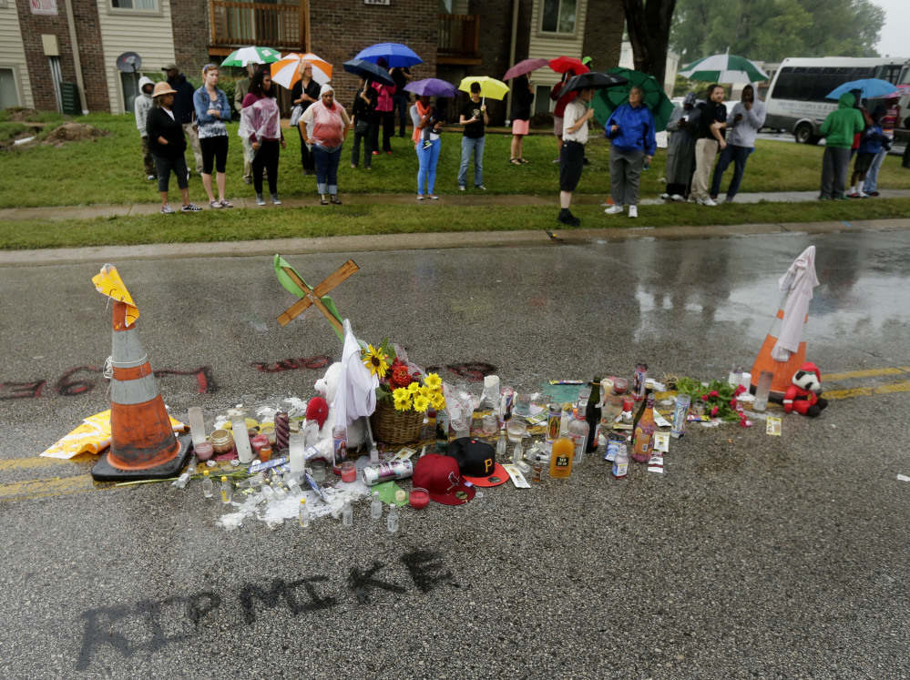 People gather next to a makeshift memorial for Michael Brown on Saturday, located at the site where Brown was shot by police a week ago in Ferguson, Mo. Brown's shooting in the middle of a street following a suspected robbery of a box of cigars from a nearby market has sparked a week of protests, riots and looting in the St. Louis suburb.
