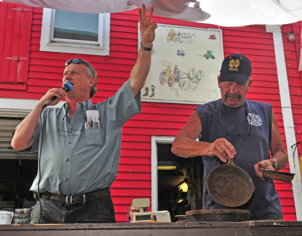 Auctioneer Brian Huntley, left, sells the collection of cast iron pans that Mike King is showing the crowd during the Coopers Mills Volunteer Fire Department charity auction on Saturday.