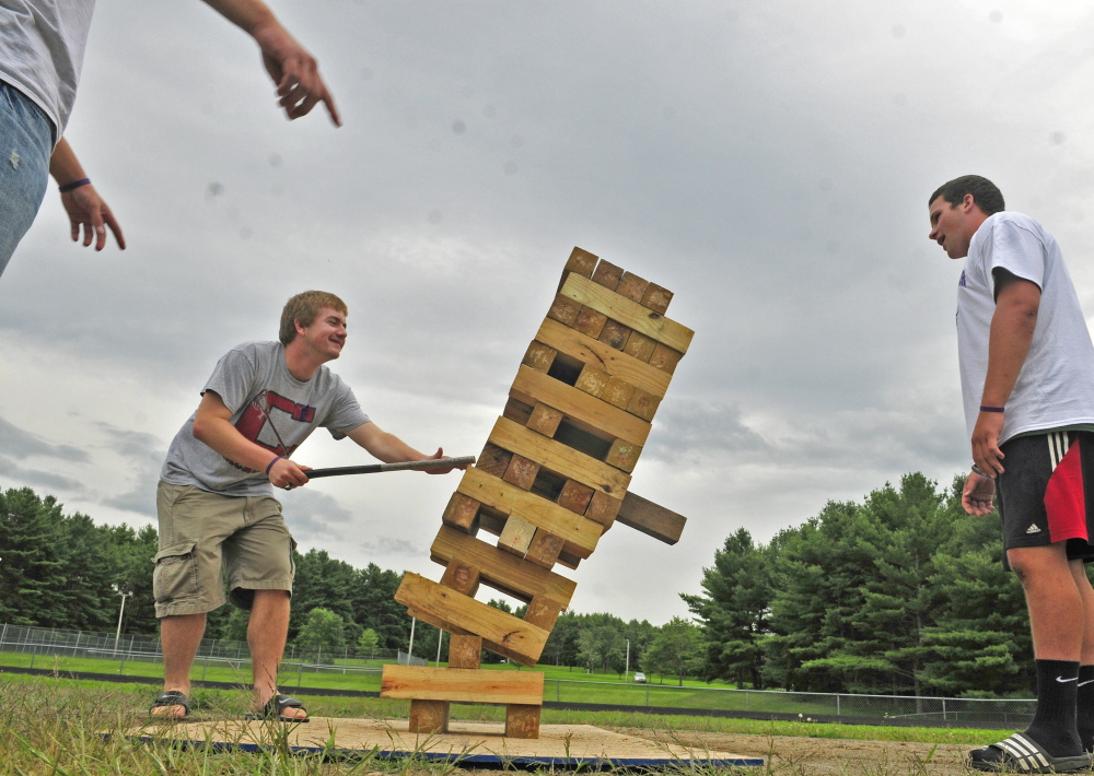 Joe Wathen, center, reacts as his last move knocks over a giant Jenga game during a fundraiser for the Lucas family on Saturday at Cony High's Alumni FIeld. Alison Lucas, mother of former Cony quarterback Ben Lucas, was recently diagnosed with cancer.