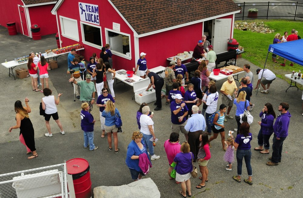 The crowd mingles around food booths during a fundraiser on Saturday at Cony High's Alumni Field. Alison Lucas, mother of former Cony quarterback Ben Lucas, was recently diagnosed with cancer.