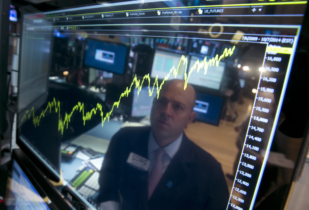 In this July 3, 2014 file photo, specialist Jay Woods is reflected in a screen at his post that shows five years of the Dow Jones industrial average, on the floor of the New York Stock Exchange.