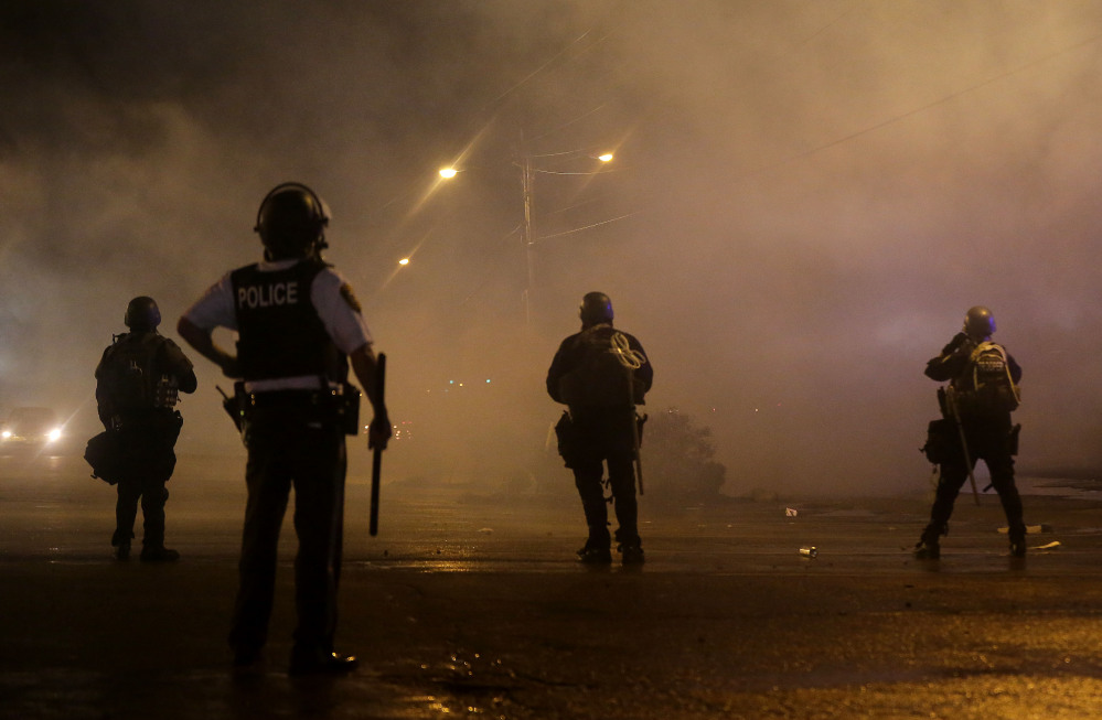 A law enforcement officer watches early Sunday as tear gas is fired to disperse a crowd protesting the shooting of teenager Michael Brown last Saturday in Ferguson, Mo.