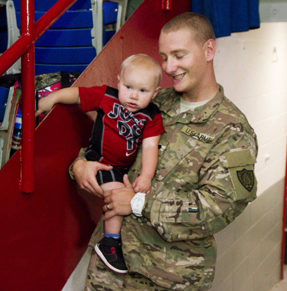Spc Devin Allen of Maine's 133rd Engineer Battalion, recently back from deployment in Afghanastan, enjoys time with his son Drake, 15 months, before being honored during a ceremony at the Colisee in Lewiston on Sunday.