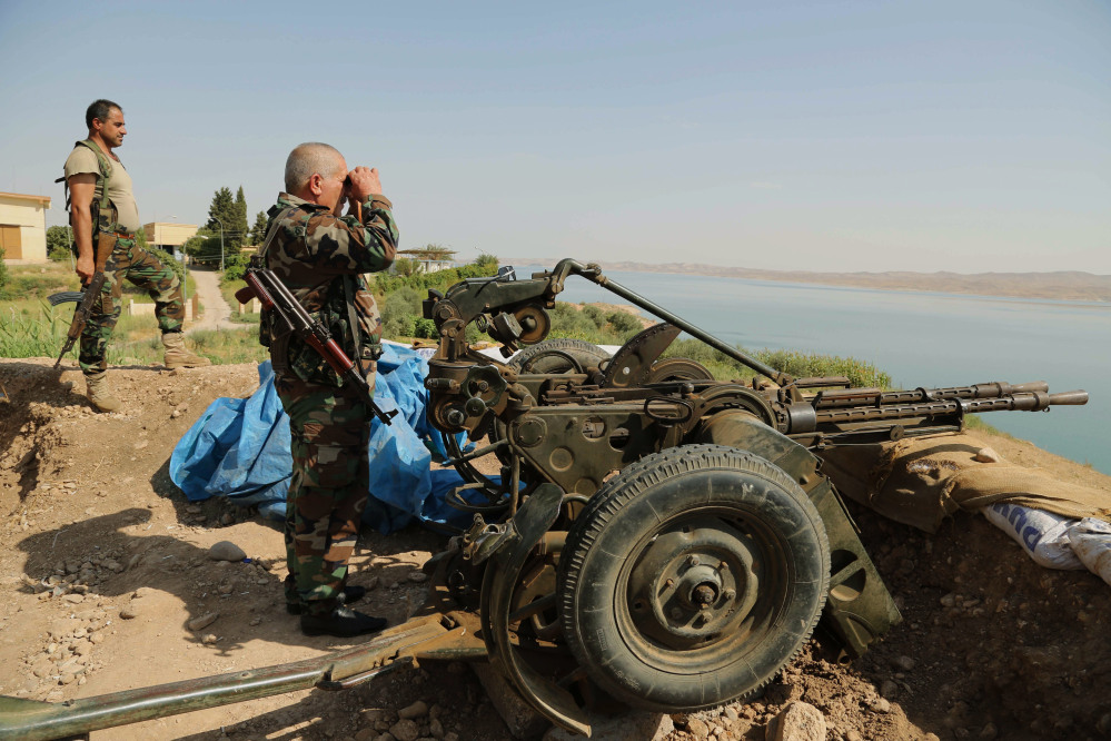 Kurdish forces, known as peshmerga, stand guard near Mosul Dam at the town of Chamibarakat outside Mosul, Iraq, on Sunday. Kurdish forces took over parts of the largest dam in Iraq on Sunday less than two weeks after it was captured by the Islamic State extremist group, Kurdish security officials said.