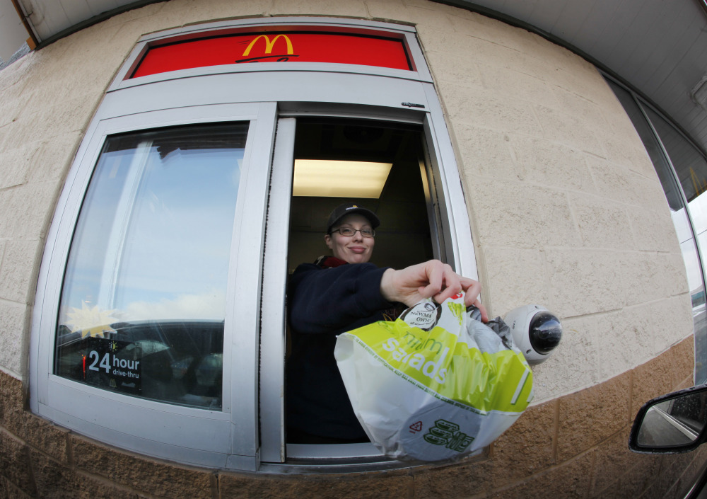 In this Jan. 26, 2009 file photo, McDonald's employee Cortney Sobowiec hands a patron a salad at the drive up window at McDonalds in Williamsville, N.Y.