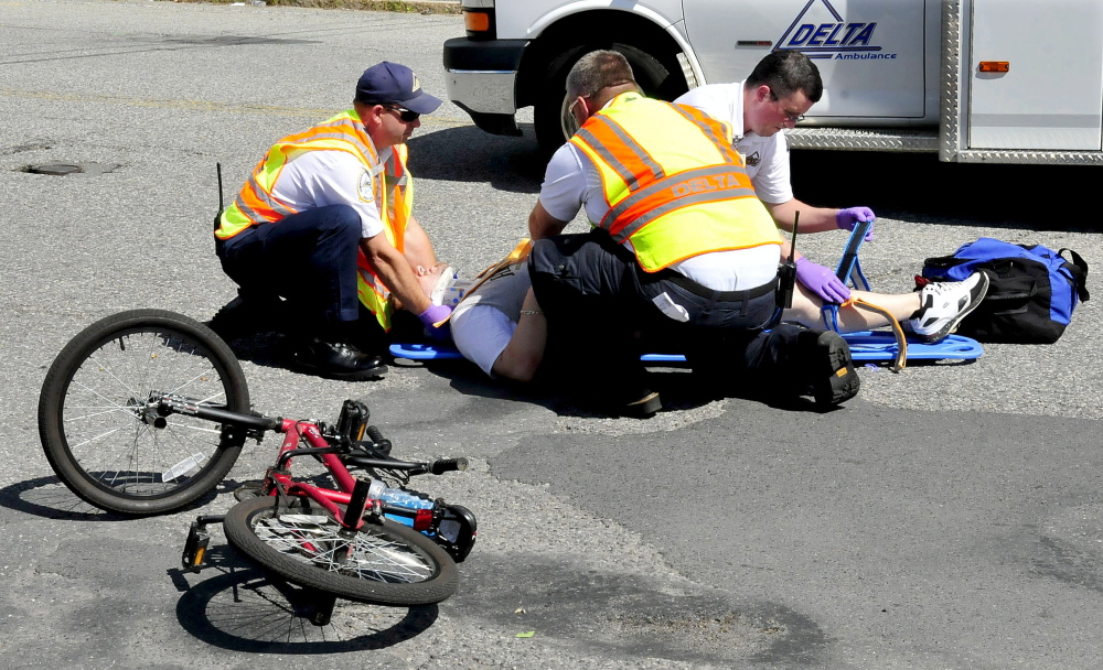 Rescue personnel treat an injured bicyclist after a collision with a vehicle on College Avenue in Waterville.