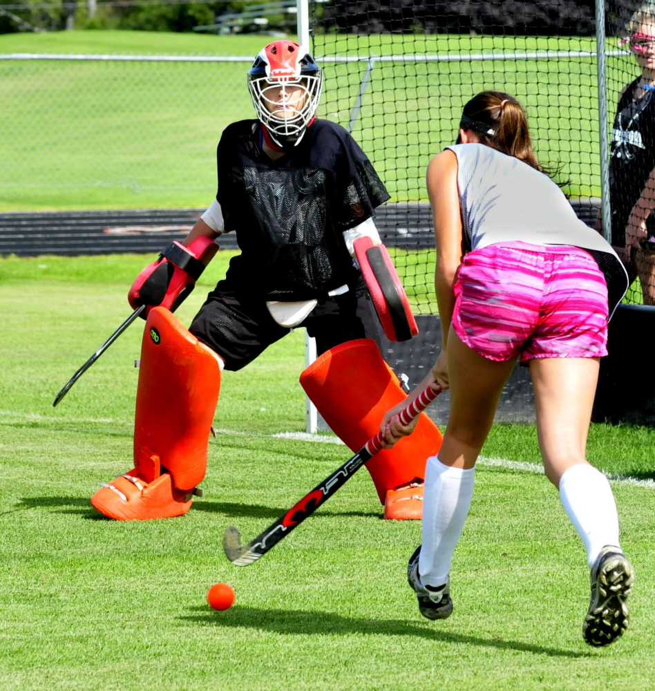 Skowhegan Area field hockey goalie Kelsey Robinson guards net as Cassidy Clements approaches during first practice of season on Monday. It was the first day of fall sports practice for schools throughout the area.