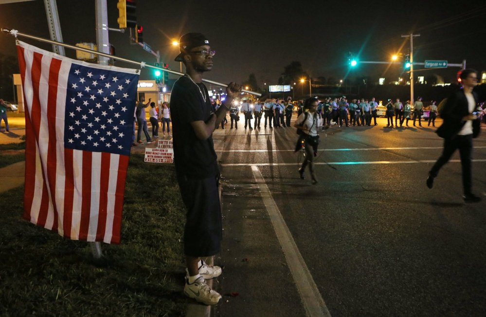 A protester watches the confrontation between the police and demonstrators Monday in Ferguson, Mo.