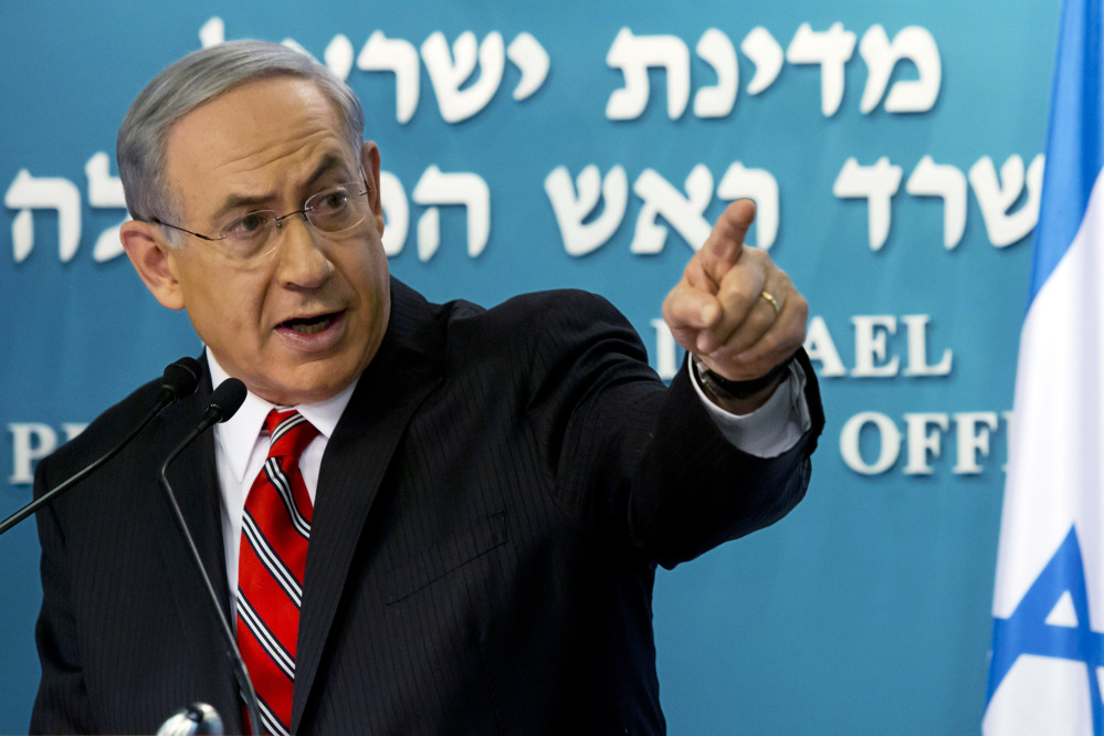 In this Aug. 6, 2014, file photo, Israeli Prime Minister Benjamin Netanyahu points at a video screen showing Hamas militants firing rockets into Israel from areas near schools and Hamas deploying civilians as human shields, as he gives a news conference in Jerusalem.