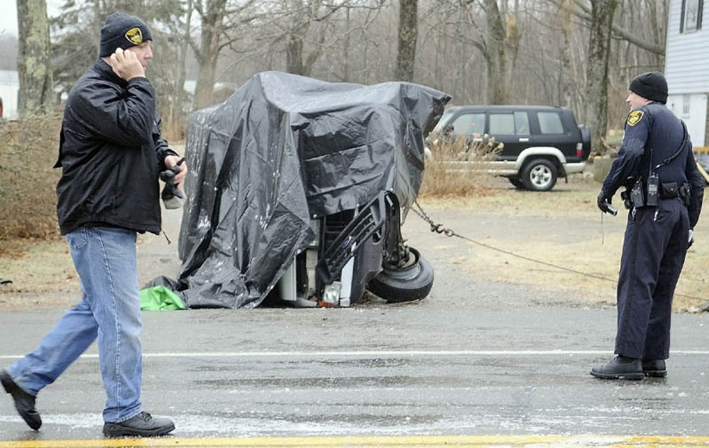 Gardiner Police Chief James Toman, left, and Officer Dan Murray investigate a rollover accident Dec. 31, 2011, that claimed the lives of two men and injured a third on U.S. Route 201 in Gardiner. The accident occurred after 8 a.m. in icy conditions.