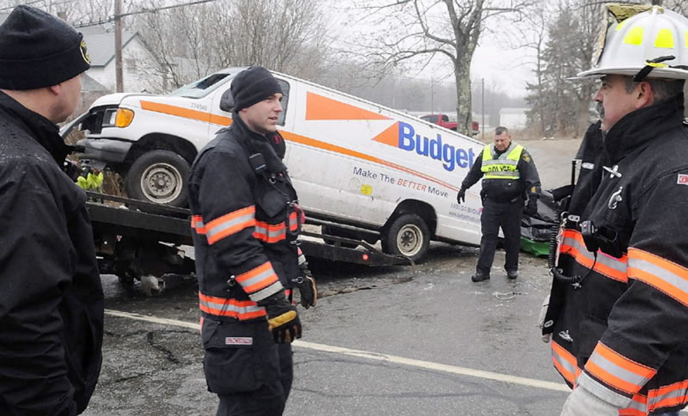 Gardiner police and firefighters remove a van that rolled over Dec. 31, 2011, and claimed the lives of two men and injured a third on U.S. Route 201 in Gardiner. The accident occurred after 8 a.m. in icy conditions.