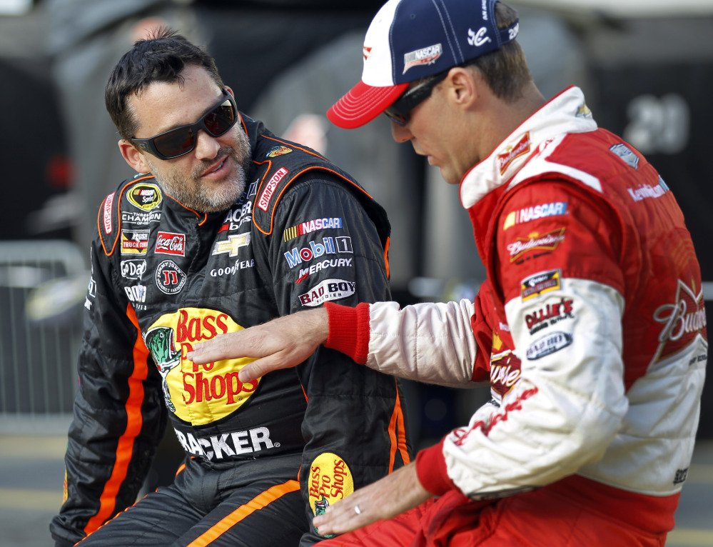 In this May 2014 photo, Tony Stewart, left, talks with Kevin Harvick before qualifying for a NASCAR Sprint Cup series auto race at Charlotte Motor Speedway in Concord, N.C. Stewart is skipping a third straight Sprint Cup race, and it is not clear when the NASCAR star might return after he struck and killed a driver at a dirt-track race in New York weeks ago.