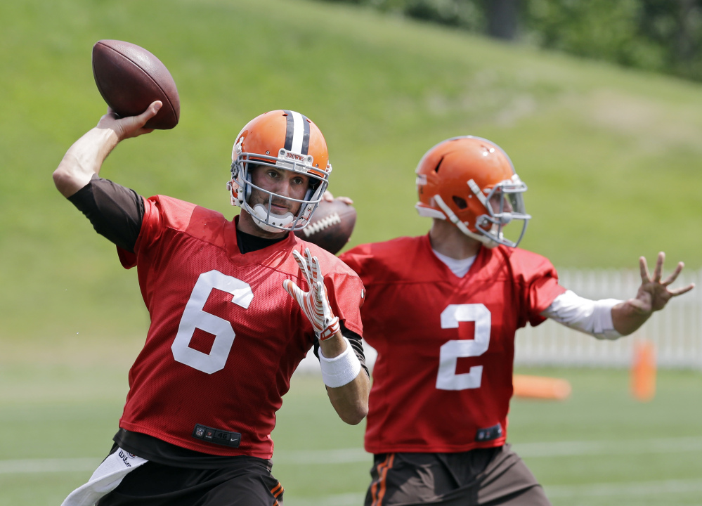 Cleveland Browns quarterback Brian Hoyer (6) passes with Johnny Manziel (2) during practice at the team's facility in Berea, Ohio on Wednesday. Hoyer was named the opening day starter.