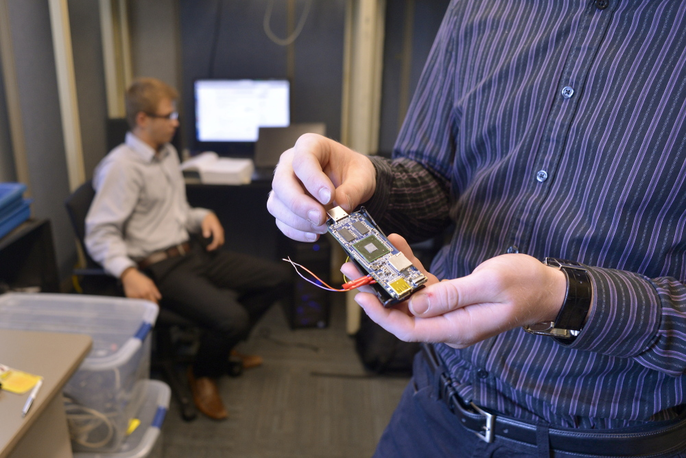 Samuel Barton, right, and Michael Guesev display a microcomputer Wednesday at the University of Southern Maine's new cybersecurity laboratory in Portland. The microcomputer is designed to set up a network of sensors for data monitoring for security purposes.