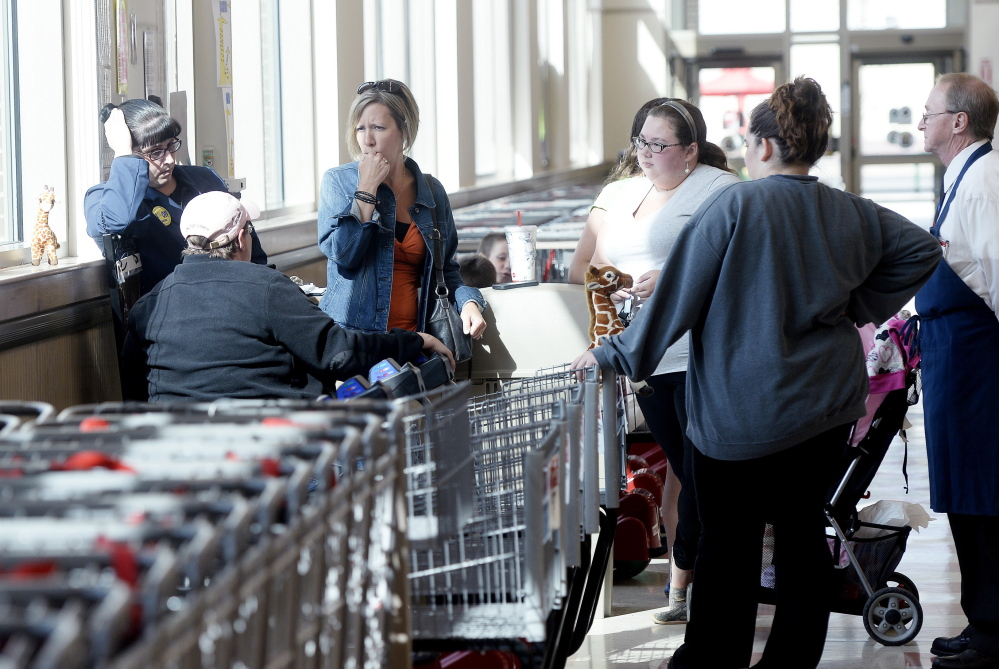 Employees gather at the front of the store at the Market Basket in Biddeford on Friday as they await news on whether their former CEO Arthur T. Demoulas will return to his former job.