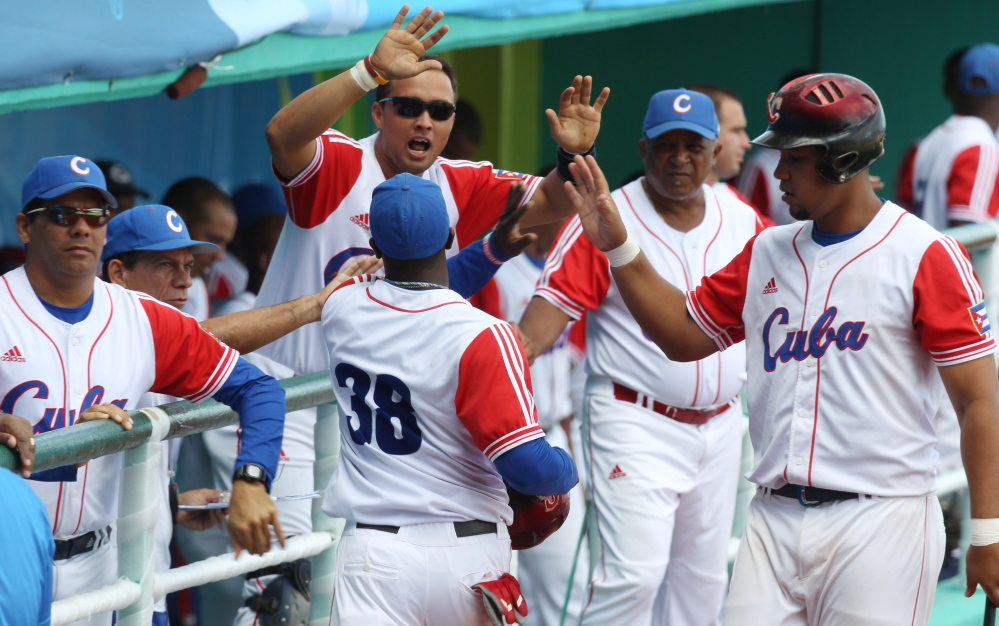 Cuba's Rusney Castillo (38) celebrates with teammates after scoring during a baseball game against Venezuela at the Pan American Games in Lagos de Moreno, Mexico. Castillo has been signed by the Red Sox, according to media reports.