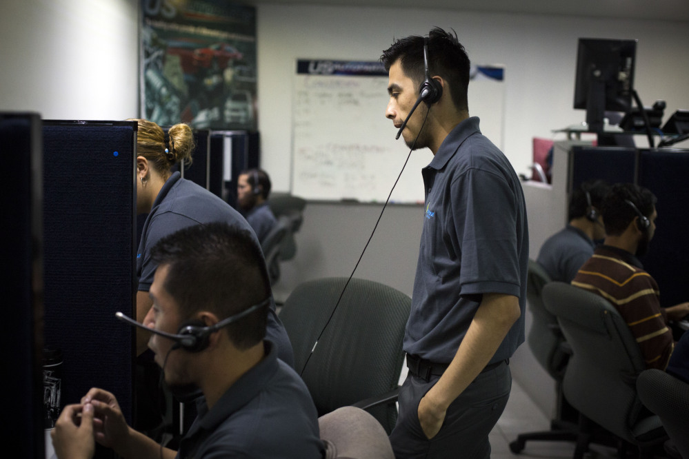 Men work the phones at the Firstkontact Center, a call center in the northern border city of Tijuana, Mexico.