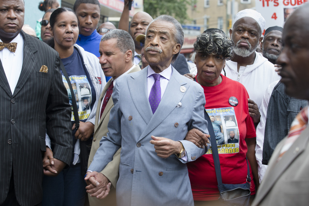 The Rev. Al Sharpton, center, holds hands with former New York Gov. David Paterson, center left, and Gwen Carr, mother of Eric Garner, alongside Esaw Garner, second from left, as they arrive before a march to protest the death of 43-year-old Eric Garner on Saturday.