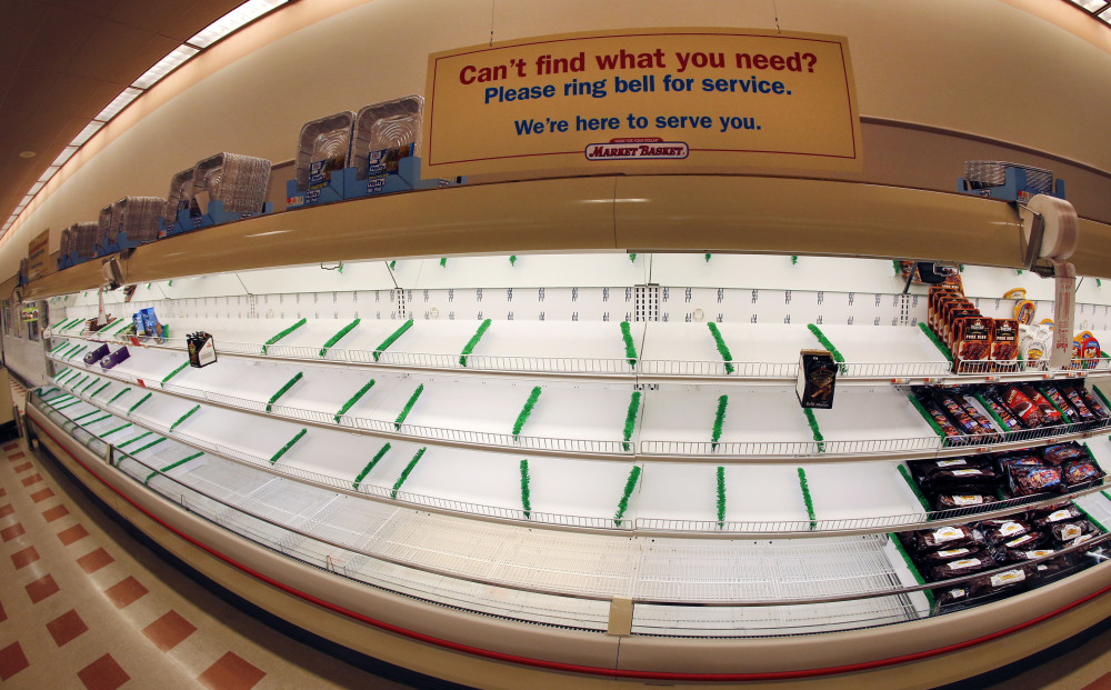 A sign sits atop mostly empty meat shelves at Market Basket in Haverhill, Mass.