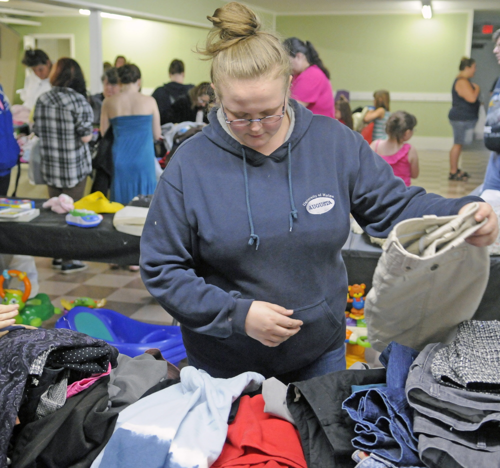 Kelly Smith, of Augusta, browses among the offerings Saturday during a clothing giveaway at Kennebec Community Church in Augusta.