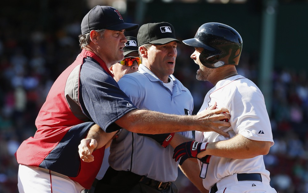 Boston Red Sox manager John Farrell, left, and home plate umpire Angel Hernandez, center, restrain David Ross after he was ejected by first base umpire Vic Carapazza during the eighth inning against the Seattle Mariners on Saturday in Boston. The Mariners won 7-3.