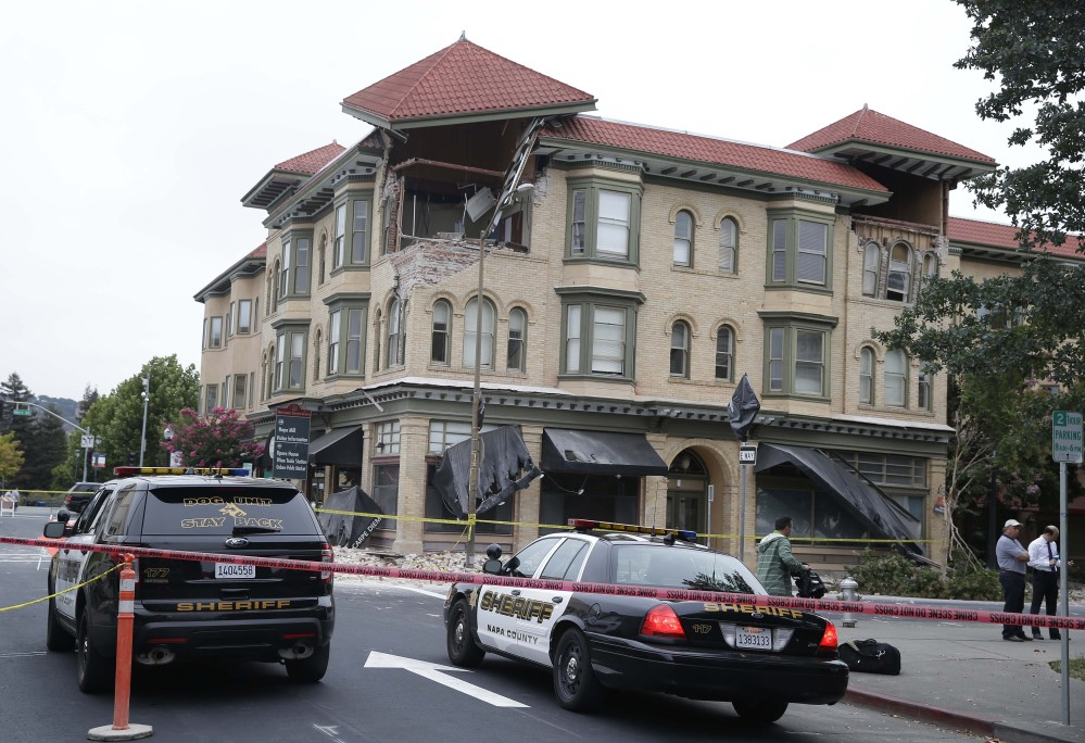 Police cars block the street outside a heavily damaged building following an earthquake on Sunday in Napa, Calif.